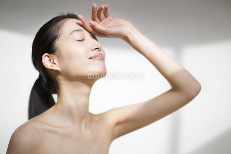 手をかざし目を瞑る女性の写真素材 [FYI02972049]