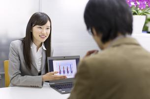 パソコンを使って接客するビジネス女性の写真素材 [FYI02972060]
