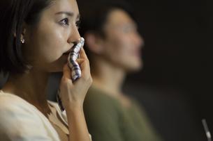 映画館で涙をこぼす女性の写真素材 [FYI02972063]