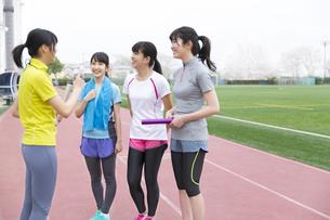 陸上競技場で話をしている女子学生たちの写真素材 [FYI02972067]