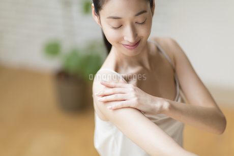 肩に手をあて微笑む女性の写真素材 [FYI02972069]