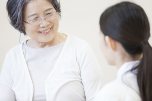 患者と話をする女性看護師の写真素材 [FYI02972070]