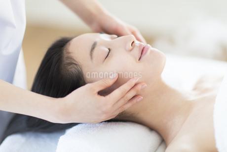 仰向けで顔をマッサージされている女性の写真素材 [FYI02972074]