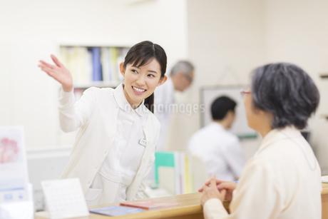 受付で患者に案内をする女性看護師の写真素材 [FYI02972078]