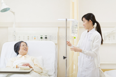 点滴を準備する女性看護婦と話をする患者の写真素材 [FYI02972085]