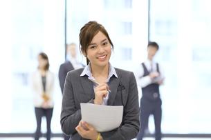 オフィスビルのロビーで資料を持って微笑むビジネス女性の写真素材 [FYI02972087]
