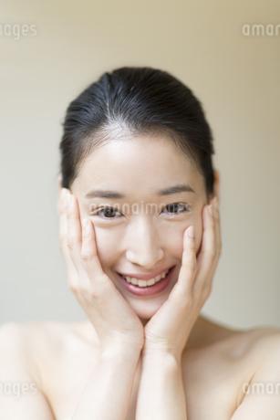 頬に両手を添えて微笑む女性の写真素材 [FYI02972089]