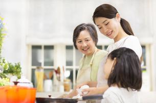 台所で会話する三世代の親子の写真素材 [FYI02972094]