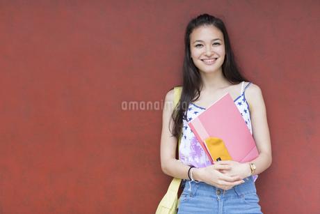 赤い壁の前で微笑む女子学生のポートレートの写真素材 [FYI02972095]