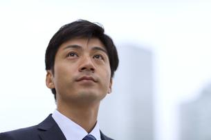 オフィスビルを背景に上を見上げるビジネス男性の写真素材 [FYI02972102]
