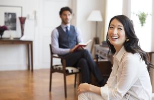 ソファーに座って微笑む女性と椅子に座って本を持つ男性の写真素材 [FYI02972110]