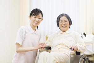 車椅子の患者の手に手を添える女性看護師の写真素材 [FYI02972112]