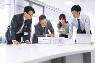 会議室で建築模型を使って打ち合せをするビジネス男女の写真素材 [FYI02972114]