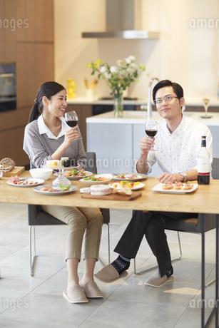 テーブルでワインを手に会話する男女の写真素材 [FYI02972115]