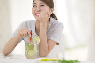 椅子に座ってデトックスウォーターを持って笑う女性の写真素材 [FYI02972116]