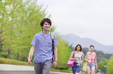 微笑みながらキャンパスを歩く男子学生の写真素材 [FYI02972117]