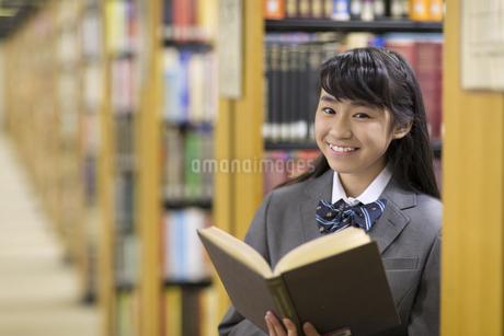 図書室で本を開いて微笑む女子高校生の写真素材 [FYI02972118]