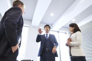 オフィスで立って打ち合わせをするビジネス男女の写真素材 [FYI02972120]