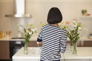 キッチンで花瓶に花を飾る女性の後ろ姿の写真素材 [FYI02972123]