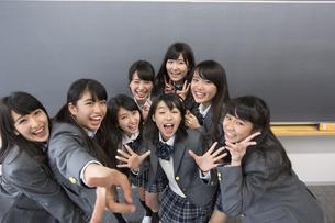 黒板の前でポーズをとる女子高校生たちのポートレートの写真素材 [FYI02972125]