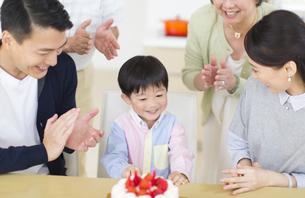 ケーキを前に誕生日のお祝いをする家族の写真素材 [FYI02972126]