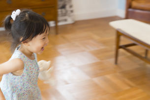 ぬいぐるみを持って走る女の子の写真素材 [FYI02972130]