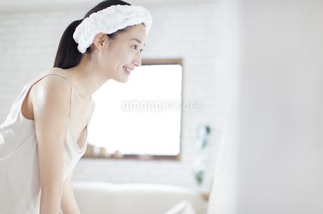 鏡の前で微笑む女性の横顔の写真素材 [FYI02972136]