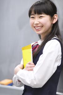 黒板の前で教材を持って微笑む女子学生の写真素材 [FYI02972137]