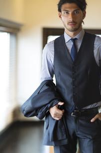 オフィスでスーツのジャケットを片手に持つビジネス男性の写真素材 [FYI02972145]