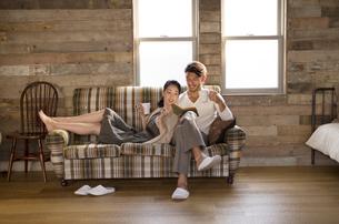 ソファーでくつろぐ男性と女性の写真素材 [FYI02972156]