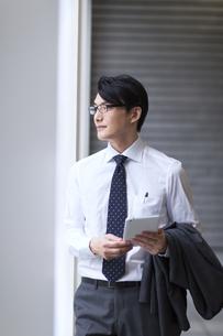 タブレットPCを持ち遠くを眺めるビジネス男性の写真素材 [FYI02972158]