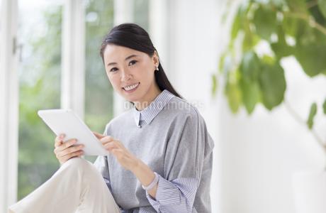 タブレットPCを手に微笑む女性の写真素材 [FYI02972160]