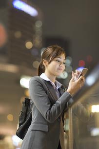 夜の街を背景にスマートフォンを見て微笑むビジネス女性の写真素材 [FYI02972163]