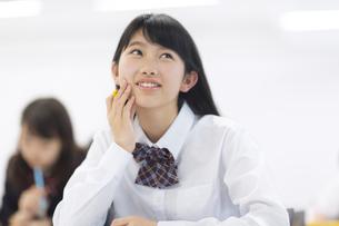 教室で頬に手を当てて考える女子学生の写真素材 [FYI02972165]