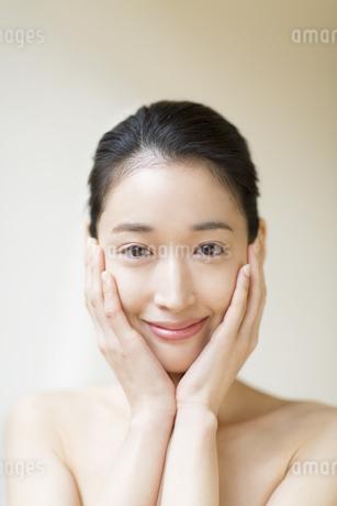 頬に両手を添えて微笑む女性の写真素材 [FYI02972166]
