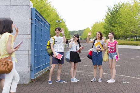 キャンパスの門で挨拶し合う学生たちの写真素材 [FYI02972167]