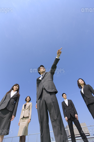 青空を背景に指をさす方向を見るビジネス男女の写真素材 [FYI02972170]