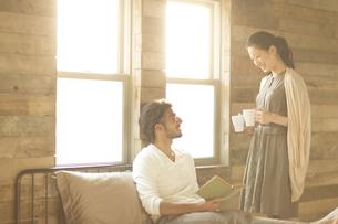 ベッドの上にいる男性にカップを手渡す女性の写真素材 [FYI02972171]