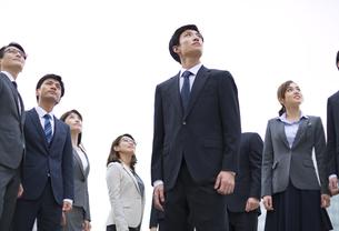 オフィスビルを背景に上を見上げて立つビジネス男女の写真素材 [FYI02972174]