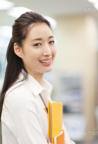 オフィスでファイルを手に微笑むビジネス女性の写真素材 [FYI02972177]