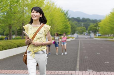 微笑みながらキャンパスを歩く女子学生の写真素材 [FYI02972185]