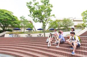キャンパスの階段に座り笑う学生たちの写真素材 [FYI02972187]