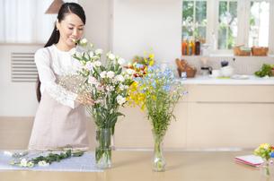 花瓶に花を飾る奥さんの写真素材 [FYI02972188]