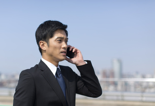 スマートフォンで話すビジネス男性の写真素材 [FYI02972189]