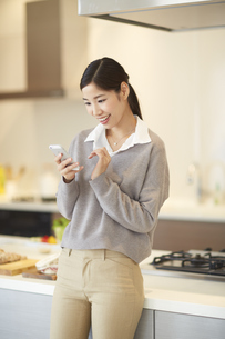 キッチンでスマートフォンを操作する女性の写真素材 [FYI02972193]