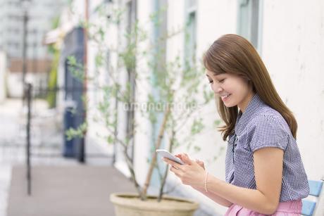 ベンチに座ってスマートフォンを操作する女性の写真素材 [FYI02972198]