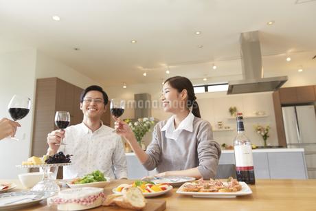 ホームパーティでワインを手に笑う男女三人の写真素材 [FYI02972207]