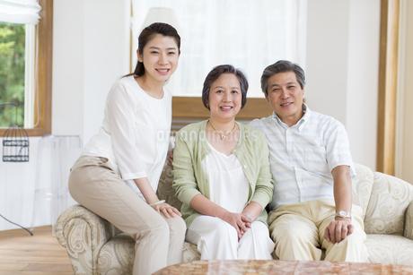 笑顔で寄り添うシニア夫婦と娘の写真素材 [FYI02972214]