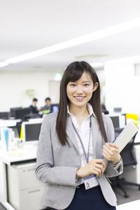 オフィスで立って微笑むビジネス女性の写真素材 [FYI02972215]