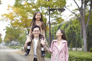 肩車して遊歩道を歩く家族の写真素材 [FYI02972222]
